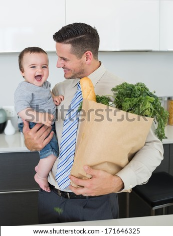 Businessman with grocery carrying cheerful baby boy in kitchen - stock photo