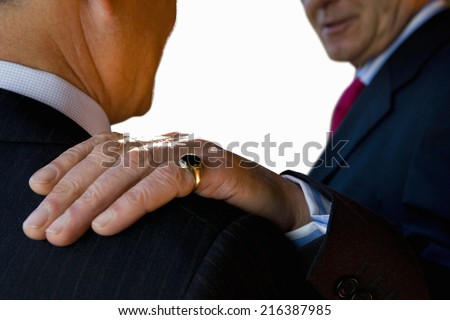 Businessman with hand on shoulder of colleague, close-up, cut out - stock photo
