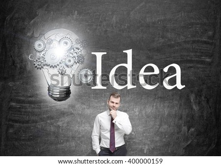 Businessman with hand to chin in front of blackboard, bulb with gears painted to the left. Concept of new idea. - stock photo