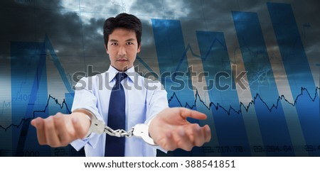 Businessman with handcuffs against blue data - stock photo