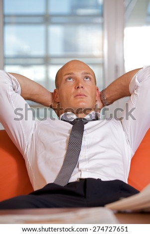 Businessman with hands behind head - stock photo