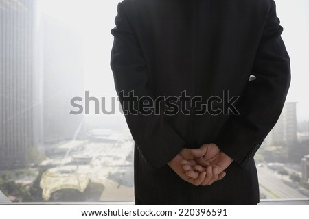 Businessman with hands clasped behind his back in front of window - stock photo