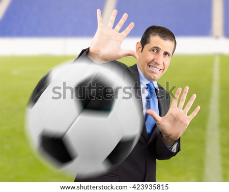 Businessman with hands in fear and goalkeeper playing football in a stadium - stock photo