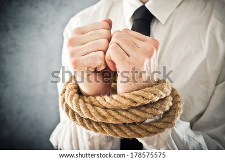 Businessman with hands tied in ropes. Business problems and difficulties, obstructions and limits in work. - stock photo