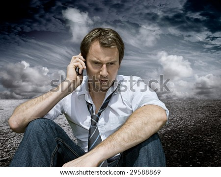 businessman with handy on a road with dark clouds behind