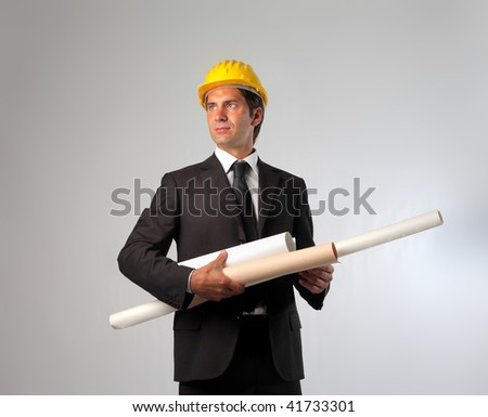 businessman with hard hat and blue print rolls - stock photo