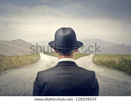 businessman with hat in front of two roads - stock photo