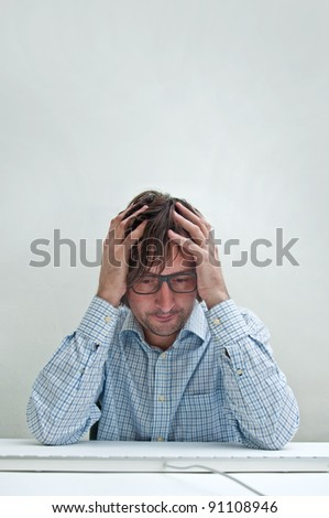 Businessman with headache looking down at the computer keyboard