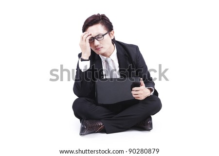 Businessman with headache sits on floor with this laptop isolated on white