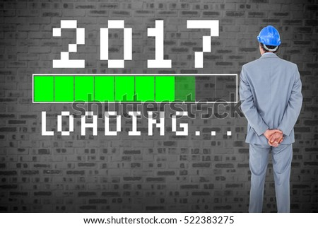 Businessman with helmet turning his back to camera against green loading display