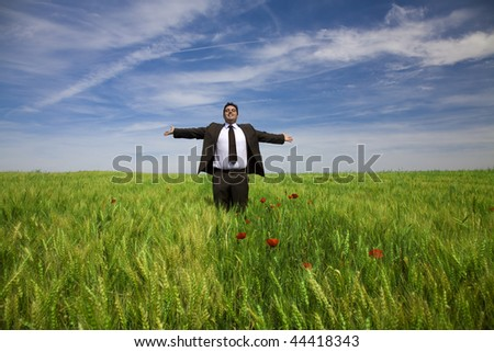businessman with his arms wide open in rural field - stock photo