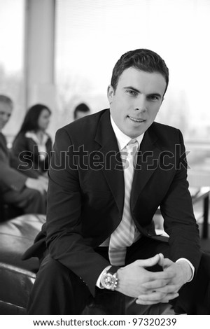 Businessman with his co-workers in office smiling - stock photo
