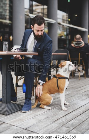 Businessman with his dog at a coffee shop.