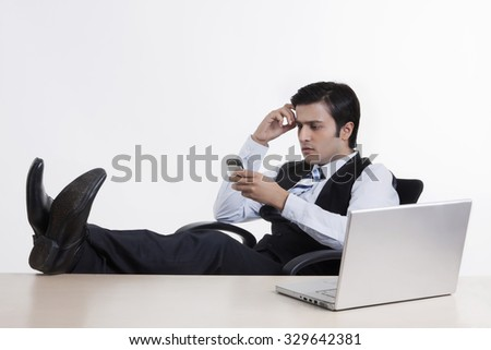 Businessman with his feet on the table - stock photo