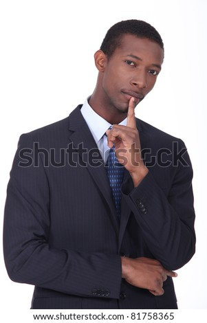 Businessman with his finger to his chin in thought - stock photo