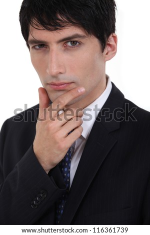 Businessman with his hand on his chin - stock photo