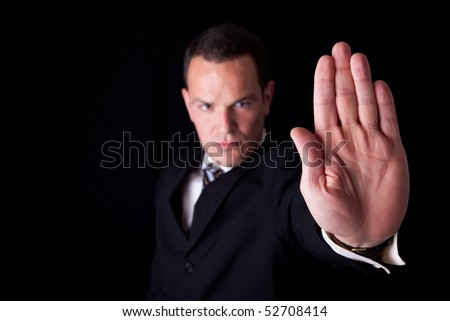 Businessman with his hand raised in signal to stop, isolated on black background, Studio shot - stock photo