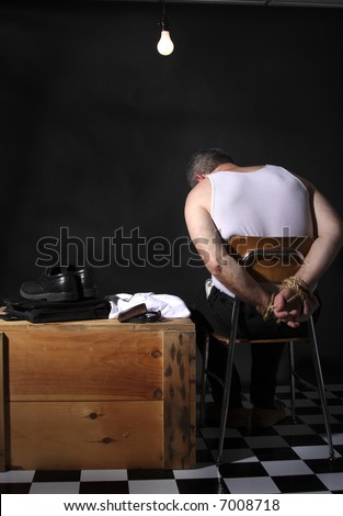 Businessman with his hands tied up sitting under a bare lightbulb in a hostage or kidnap situation. - stock photo