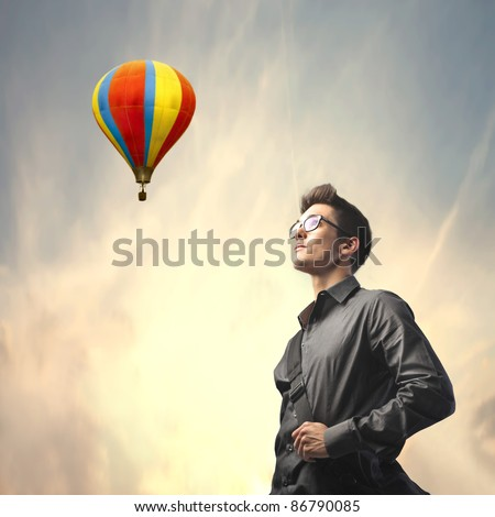 Businessman with hot-air balloon in the background - stock photo