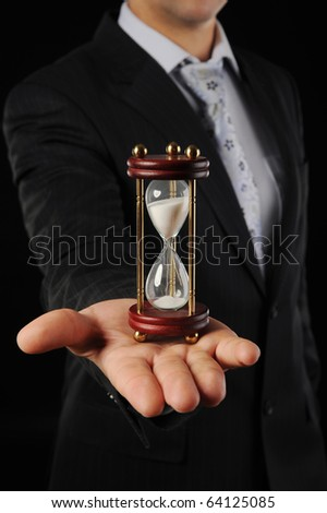 Businessman with hourglass in hand in a dark room - stock photo