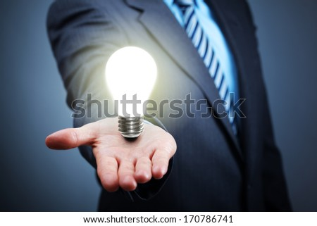 Businessman with illuminated light bulb balancing on his hand concept for idea, innovation and inspiration - stock photo