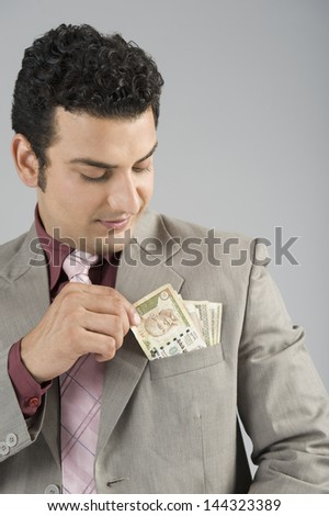 Businessman with Indian five hundred rupee banknotes in his pocket - stock photo