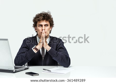 Businessman with intense expression looking up into the corner on gray background / depression and crisis concept
