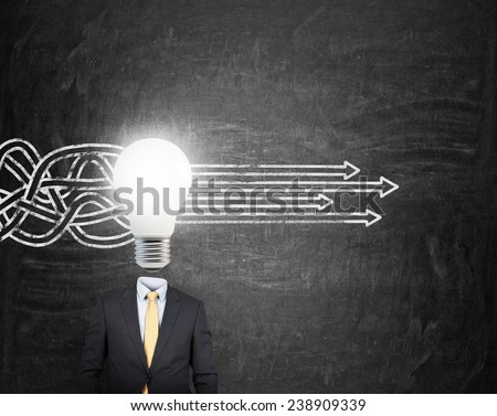businessman with lamp head and drawing arrow on wall - stock photo