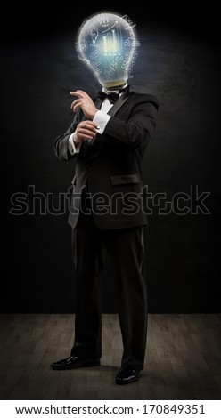 Businessman with lamp head on black background planning future. We could see his minds. Full length