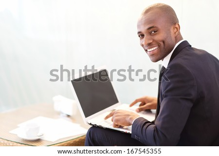 Businessman with laptop. Cheerful young African businessman typing something on laptop and looking over shoulder - stock photo