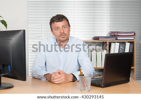 Businessman with laptop computer and documents at office