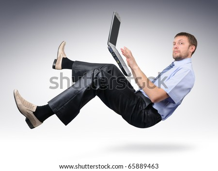 Businessman with laptop computer unreal pose in air (concept) - stock photo