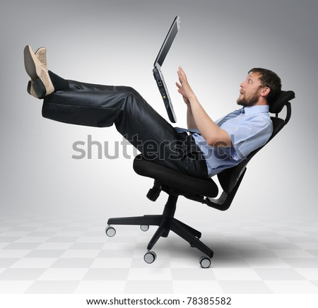 Businessman with laptop falls from an office chair, concept - stock photo