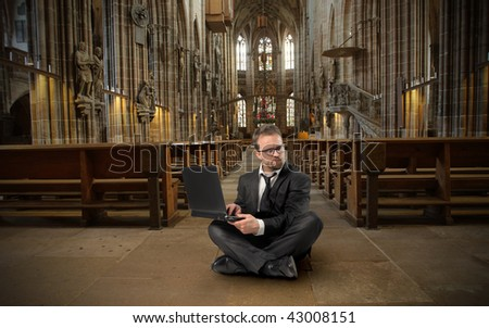 businessman with laptop in a church - stock photo