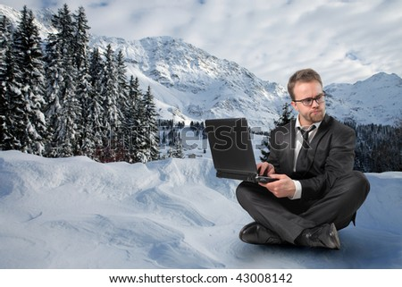 businessman with laptop in a snowy landscape - stock photo