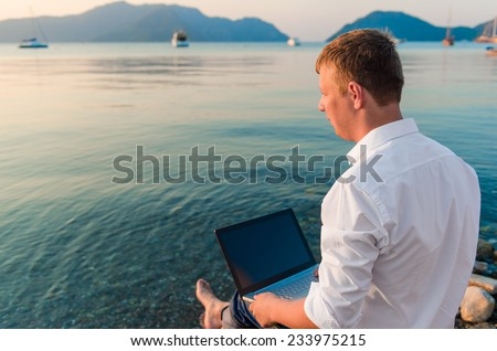 businessman with laptop looking at the sea - stock photo