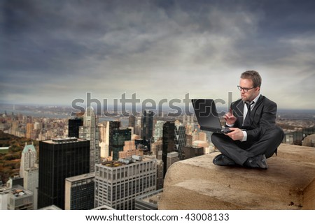 businessman with laptop on the top of new york building - stock photo
