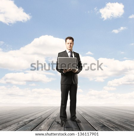 businessman with laptop on wood floor and blue sky background
