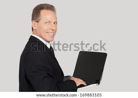 Businessman with laptop. Rear view of senior man in formalwear typing something on laptop and looking over shoulder while standing against grey background - stock photo