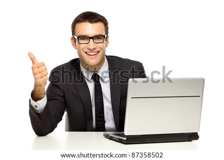 Businessman with laptop showing thumbs up - stock photo