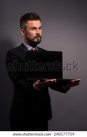 Businessman with laptop. Side view image of handsome businessman in formalwear showing a screen of his laptop for copy space while standing against grey background - stock photo