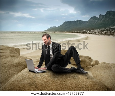 Businessman with laptop sitting on a rock looking over a seascape - stock photo