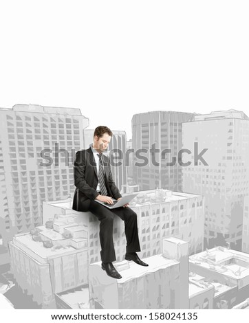 businessman with laptop sitting on building