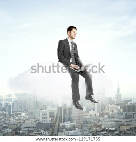 businessman with laptop sitting on cloud and city - stock photo