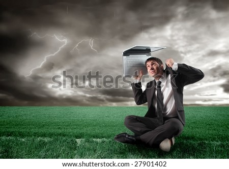 businessman with laptop under a storm - stock photo