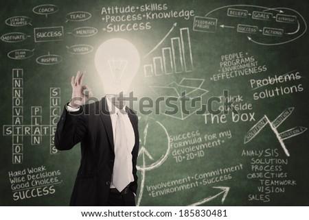 Businessman with lightbulb head in classroom - stock photo
