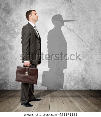 Businessman with long nose on his shadow - stock photo