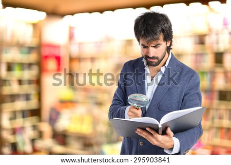 Businessman with loupe reding a book over defocused library - stock photo