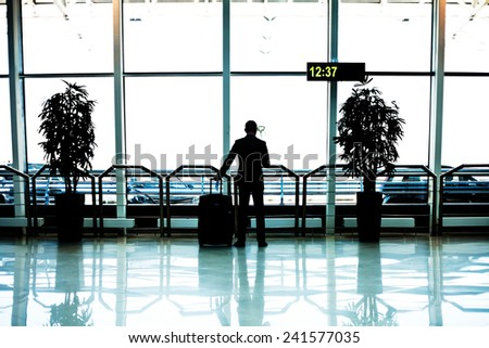 businessman with luggage in airport - stock photo