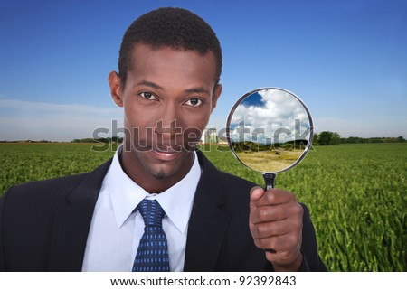 Businessman with magnifying glass - stock photo